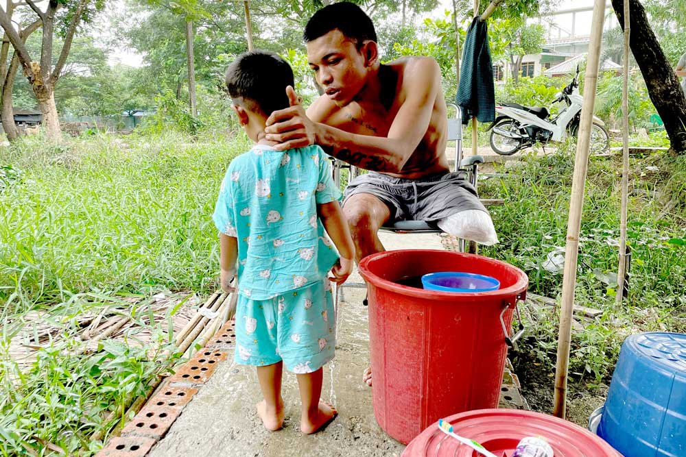 """Ko Phyo prepares to take a shower with his 2-year-old son, Paing Phyo Oo, at his home. """"I feel terrible when he asked, 'Dad, where's your leg?',"""" Ko Phyo says. """"So, I replied, 'A dog's eaten my leg but it will grow later.' And he still believes it."""" (REUTERS)"""
