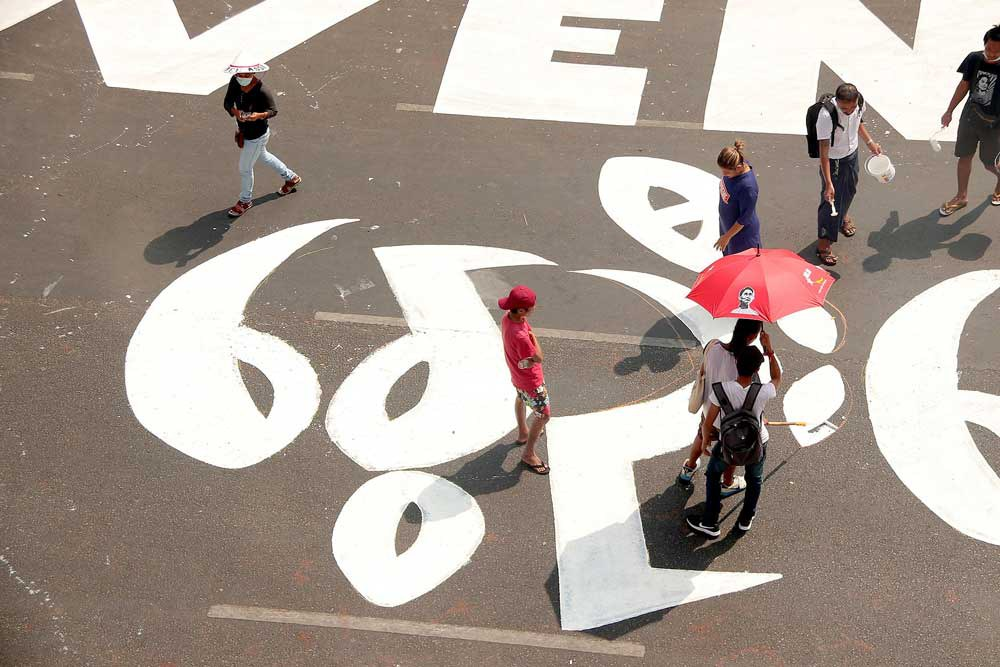 Protesters scale up their message on a street in downtown Yangon.  (RFA)