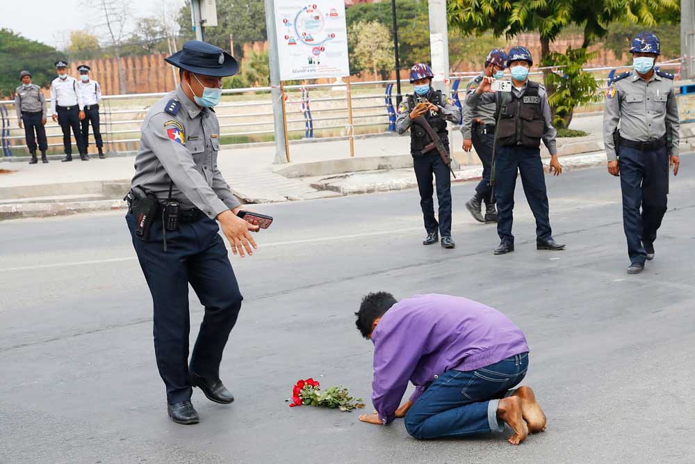 A protest supporter offers flowers and kneels on a road before a police officer in Mandalay in early February. (Associated Press)