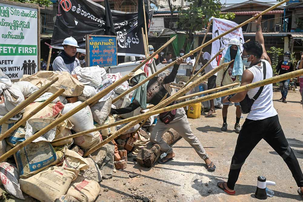 Protesters reinforce their barricade with wooden stakes to fend off security forces during a crackdown in Yangon this week. (AFP)