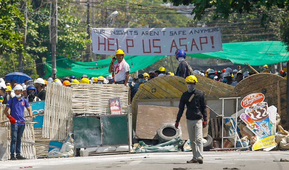 Protestors stand on a makeshift barricade as they prepare to face off against security forces during a demonstration in Yangon. (AFP)