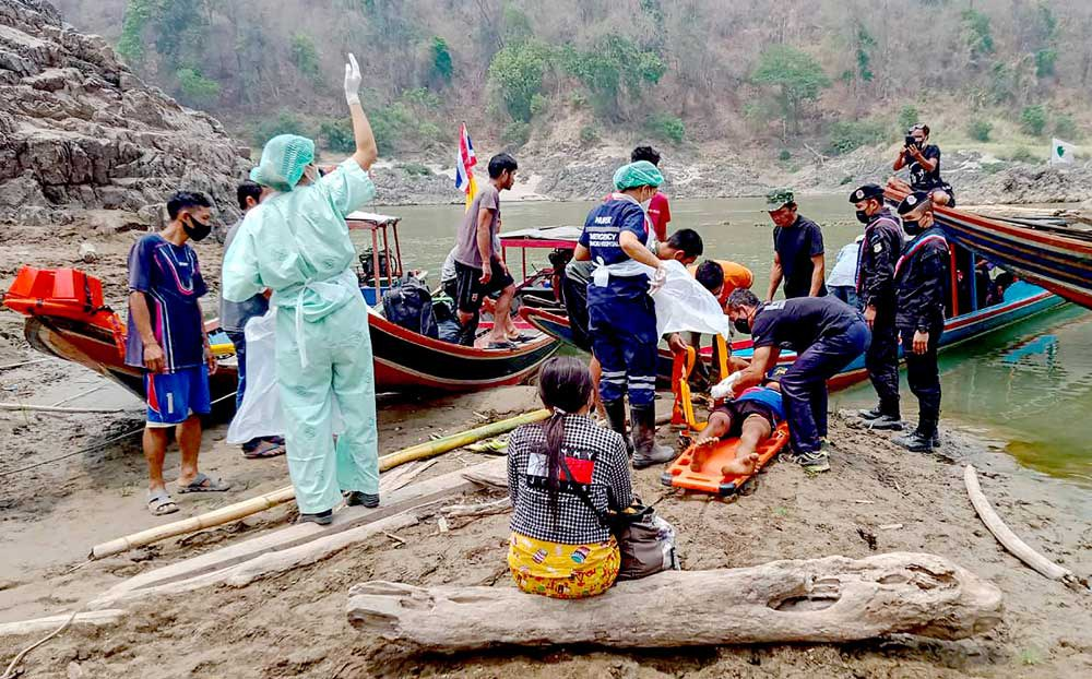 An injured refugee is placed on a stretcher Tuesday before being taken to a hospital in Mae Sam Laep, Thailand, after crossing the Salween River. (AFP/Royal Thai Army)