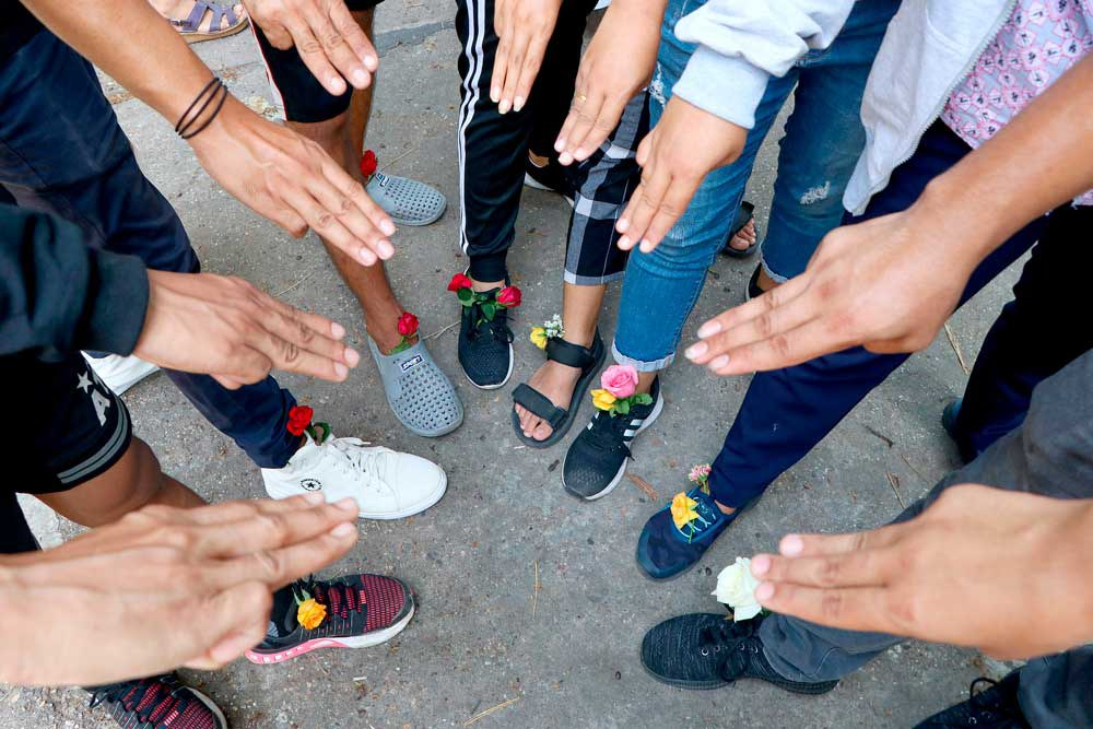 A group of protesters shows the three-fingered symbol of resistance and wear flowers in their shoes as they gather in Yangon. They later walked through the markets and streets of Kamayut township to show their resistance to coup. (Associated Press)