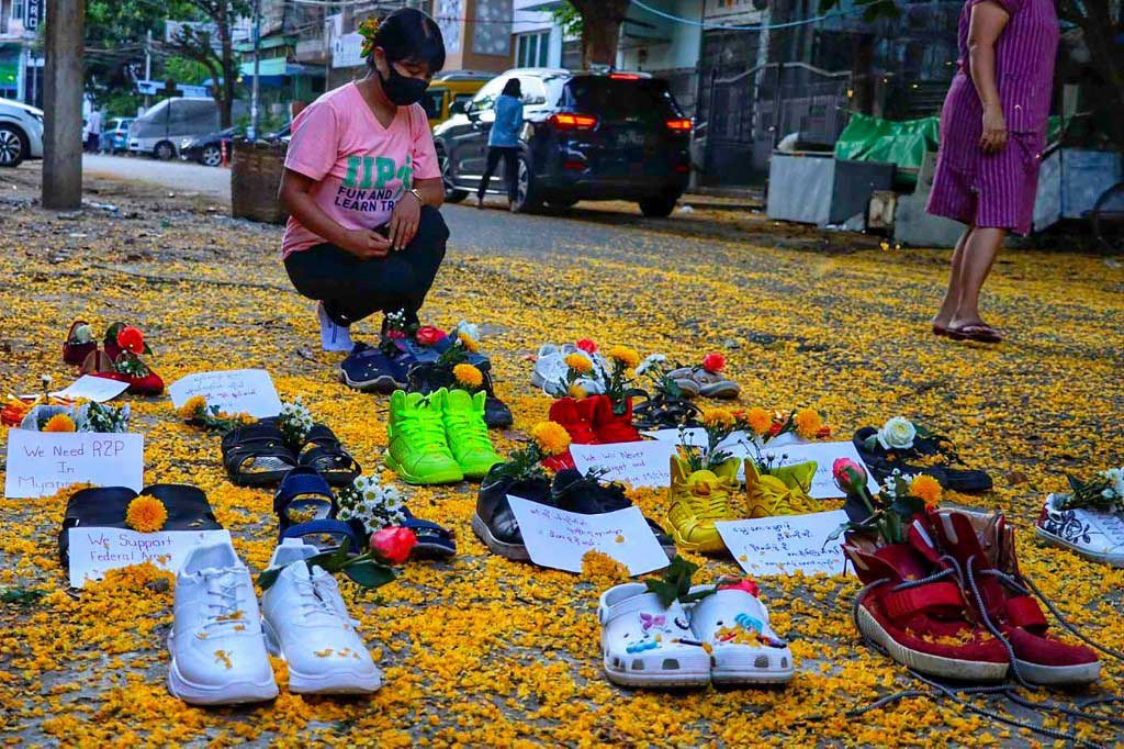 A woman looks at a tableau of shoes in Yangon's Myaynigone township. (AFP/Handout)