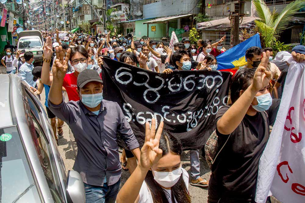 """Anti-coup protesters carry a banner that reads """"What are these? We are Yangon residents!"""" as they march during a demonstration in Yangon, Myanmar. (Associated Press)"""