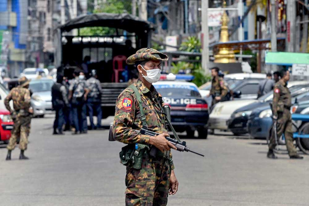 Security forces search for demonstrators as a soldier stands guard along a road in Yangon. (AFP)