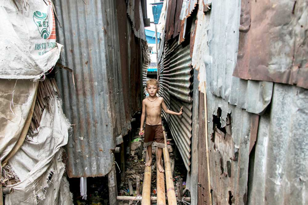 A boy walks on a bamboo bridge near his home on the outskirts of Yangon. (AFP)