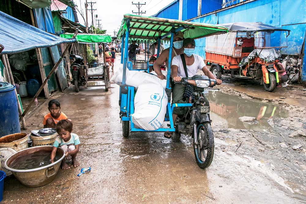 Men transport bags of rice distributed by the World Food Programme. (AFP)