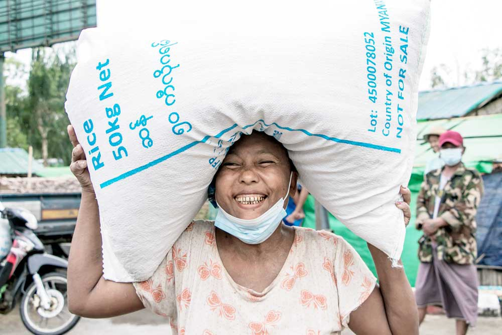 A woman smiles after receiving a bag of rice from the World Food Programme. WFP says it is increasing the number of people it assists in Myanmar from 1.3 million to 3.3 million. (AFP)