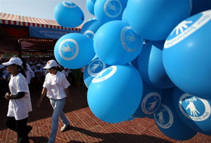 PHNOM PENH, Cambodia – Women walk past balloons bearing