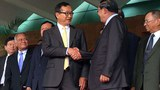 Sam Rainsy (L) shakes hands with Hun Sen following a meeting in Phnom Penh, July 22, 2014.