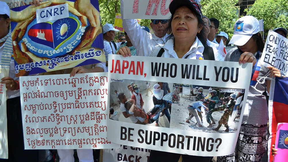 Protesters hold signs calling on Japan to withdraw support for Cambodia's elections in New York, June 16, 2018. Credit: RFA