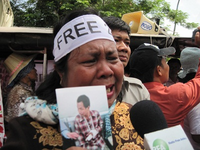 A mother of one of the 21 detainees cries as she holds a photo of her son while protesting outside the Appeals Court in Phnom Penh, Feb. 11, 2014. Photo credit: RFA.