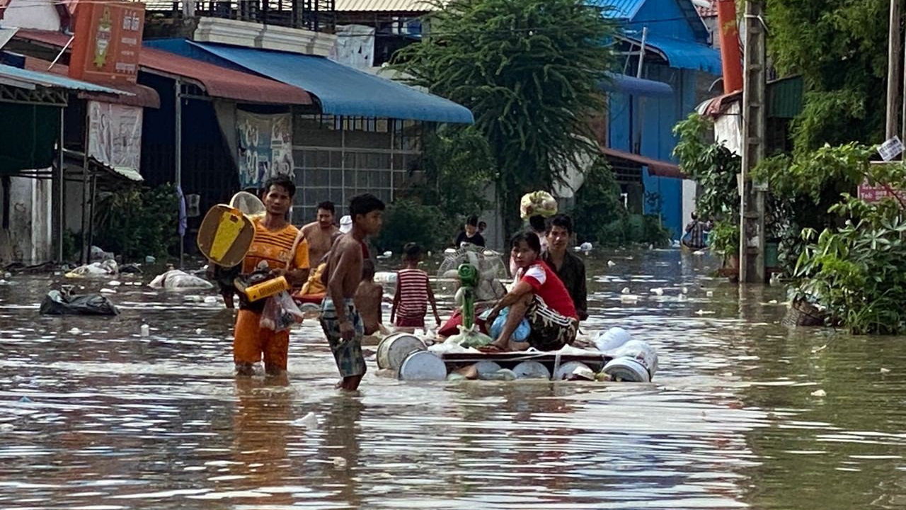 Residents carry belongings by hand and on makeshift rafts through flooded streets in Phnom Penh, Oct. 14, 2020.