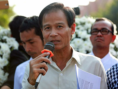 Ath Thon, president of the Coalition of Cambodian Apparel Workers' Democratic Union, talks to reporters outside the Royal Palace in Cambodia's capital Phnom Penh, Feb. 7, 2014.