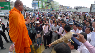 A monk blesses Mam Sonando's supporters outside the Phnom Penh Municipal Court, Sept. 11, 2012.
