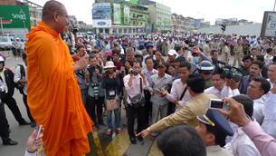 A monk blesses Mam Sonando's supporters outside the Phnom Penh Municipal Court, Sept. 11, 2012.