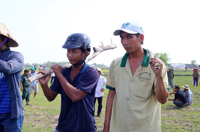 Vietnamese villagers hold sticks during a confrontation with Cambodian activists in Svay Rieng province's Kampong Ro district, June 29, 2015. Credit: RFA