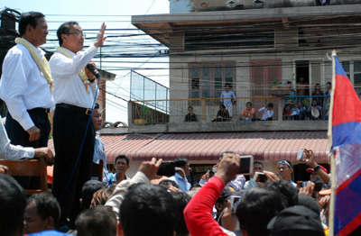 CNRP leaders Sam Rainsy and Kem Sokha address supporters outside the party headquarters, March 30, 2014. Photo credit: RFA.