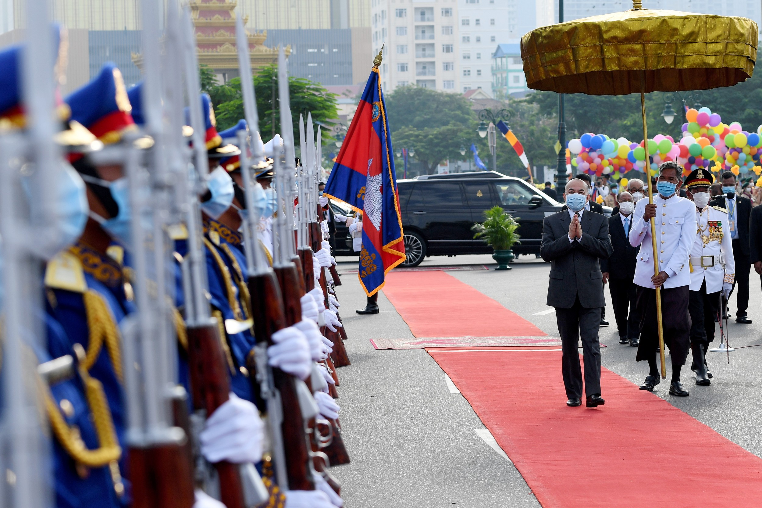 Cambodian King Norodom Sihamoni (R) walks past honor guards during a ceremony marking Cambodia's Independence Day in Phnom Penh, Nov. 9, 2020.