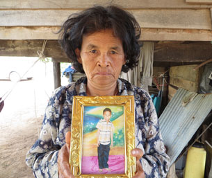 Moeun Mat's grandmother holds a picture of the young victim at the family's home in Banteay Meanchey province, Dec. 6, 2012.