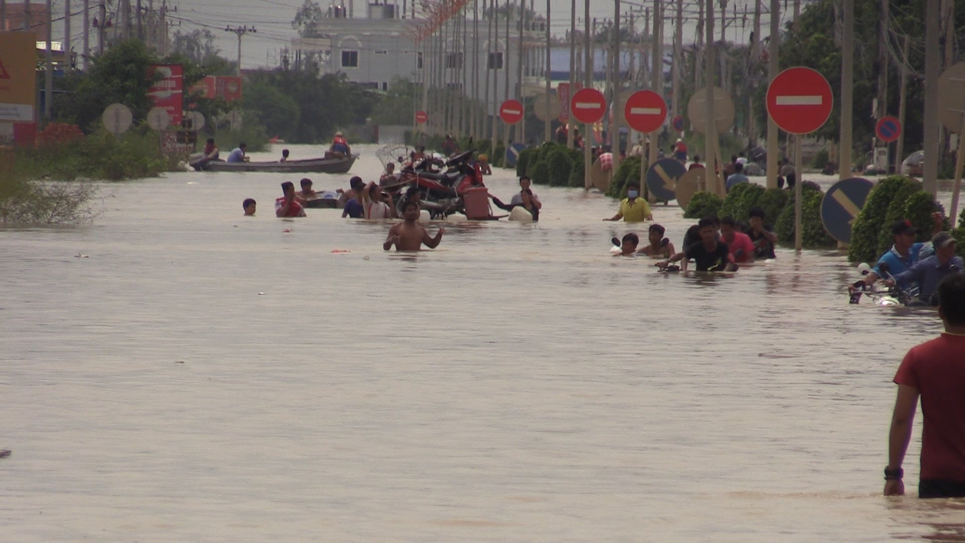 Residents wade through chest-high floodwaters in the streets of Phnom Penh, Oct. 15, 2020.