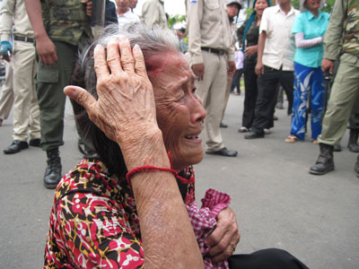 An elderly woman holds her head after receiving a blow in a struggle with a police officer, April 21, 2011.