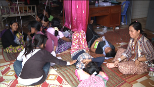 Workers receive treatment after a mass fainting at a factory outside of Phnom Penh, Oct. 27, 2011.