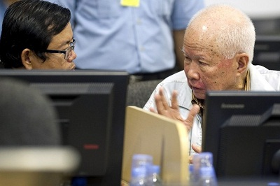 Khieu Samphan (left) speaks to his lawyer in the ECCC courtroom in Phnom Penh on Oct. 16, 2013. Photo credit: AFP  Photo / ECCC / Mark Peters.