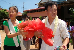 Leang Sokchouen (r) receives flowers from LICADHO President Pung Chhiv Kek (l) outside the Kandal provincial prison upon his release, May 30, 2012. RFA
