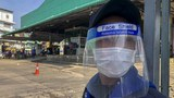 In this Dec. 20, 2020, file photo, a guard with a face-shield stands near a shrimp market in Samut Sakhon, south of Bangkok. Thailand, which has kept the coronavirus largely in check for most of the year, is facing a challenge from a large outbreak of the virus among migrant workers in the province close to Bangkok