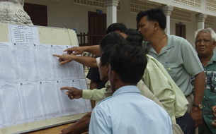 Commune councilors look at voter lists at a polling station during Cambodia's Senate election, Jan. 29, 2012.