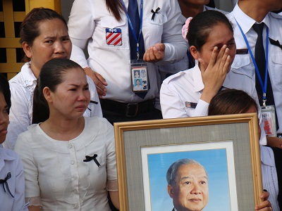 Weeping mourners hold a portrait of Sihanouk as they watch the procession of his casket from the airport in Phnom Penh, Oct. 17, 2012.