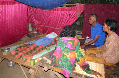 Family members keep vigil over the body of Tim Tuoy in Roka commune, March 2015. Credit: RFA