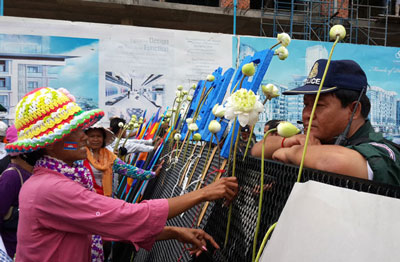 A supporter places a flower in front of security personnel outside the court in Phnom Penh, May 6, 2014. Credit: RFA
