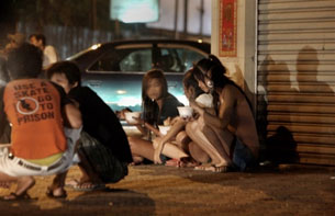 Cambodian sex workers sit on the side walk along a street in Phnom Penh on Dec. 18, 2008. AFP