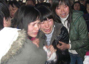 Friends grieve at the funeral of a 21-year-old Chinese woman who died following a forced abortion in Liuyang City, Hunan Province, in February 2009.