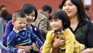 Chinese mothers hold their children at a kindergarten in Jiangsu province, Oct. 27, 2012.