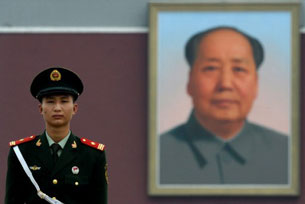 A Chinese policeman stands in front of a portrait of Mao Zedong at Tiananmen Gate in Beijing, Aug. 17, 2008.
