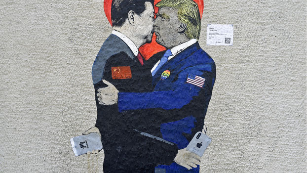 A mural depicting China's President Xi Jinping (L) holding an Apple iPhone kissing US President Donald Trump (R) holding an Huawei smartphone is displayed on a wall in Milan, Italy, June 29, 2019.