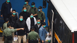 Hong Kong pro-democracy politicians and activists are escorted to a police van at the end of a bail hearing that saw all back behind bars, March 4, 2021.