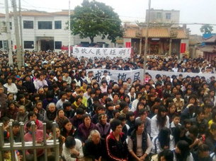 A cell phone photo shows thousands of villagers protest a land grab by local officials in Wukan, Dec. 14, 2011.
