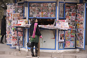 A woman looks at newspapers and magazines on one of Beijing's many news stands, Dec. 3, 2008. AFP/Peter Parks