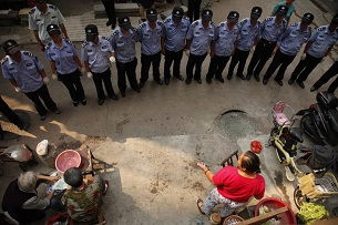 A row of chengguan stare in silence at an unlicensed street vendor in Wuhan on Sept. 19, 2012, as part of a campaign to avoid the use of force in city management.