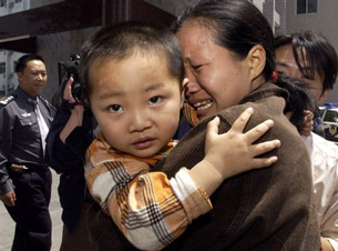 A woman cries as she is reunited with her son after he was rescued from a group of human traffickers in central China's Henan province, May 6, 2005.