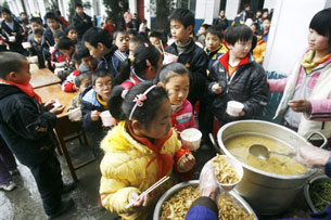 Chinese students line up to receive lunch at a school for children of migrants in Wuhan, central China's Hubei province, Feb. 17, 2009.