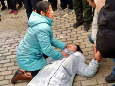 The daughter of Chinese rights lawyer Shu Xiangxin is beaten unconscious outside the Licheng District People's Court in Jinan, Shandong province, Jan. 8, 2016. Credit: Courtesy of a rights activist
