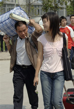A father carries baggage for his daughter as she arrives to begin the college year. Photo: AFP