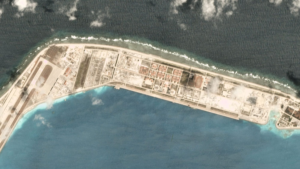 A satellite image taken March 19, 2020, over the Chinese-occupied base at Mischief Reef, showing a large vessel at the quayside. Ship-tracking software shows that Chinese Coastguard ship 5302 stopped there that day.