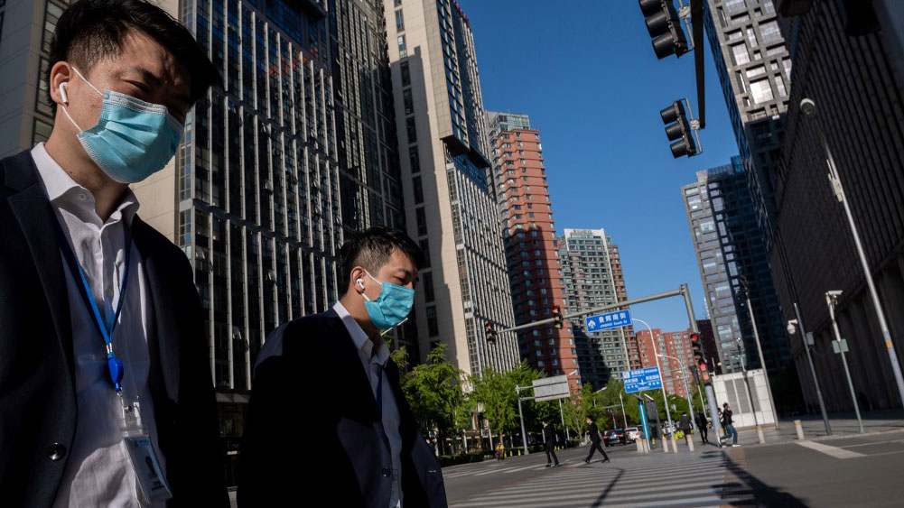 People wearing face masks amid the concerns over the COVID-19 coronavirus walk on a nearly empty street in the Chinese capital Beijing, April 23, 2020.
